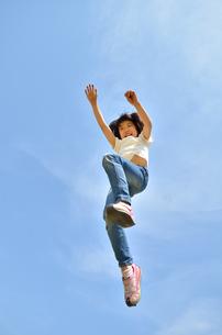 青空でジャンプする女の子の写真素材 [FYI02912924]