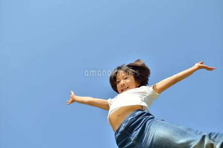 青空でジャンプする女の子の写真素材 [FYI02912925]