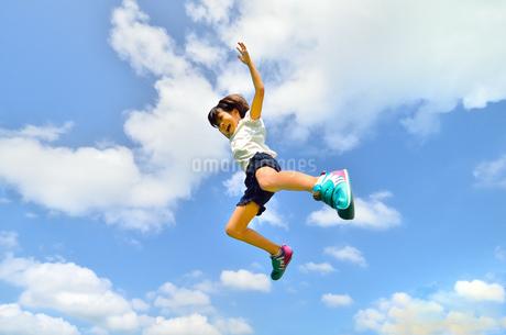 青空でジャンプする女の子の写真素材 [FYI02912926]