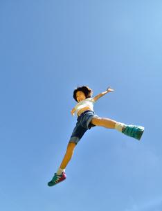 青空でジャンプする女の子の写真素材 [FYI02912927]