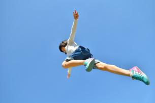 青空でジャンプする女の子の写真素材 [FYI02912928]