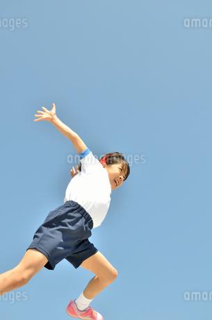 青空でジャンプする女の子(運動会、体操服)の写真素材 [FYI02912929]