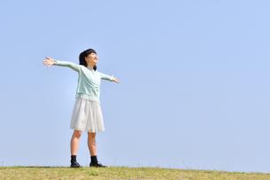 青空で両手を上げる女の子(芝生広場)の写真素材 [FYI02915014]