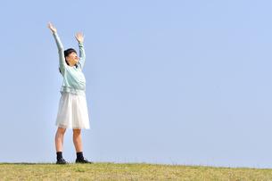 青空で両手を上げる女の子(芝生広場)の写真素材 [FYI02915016]