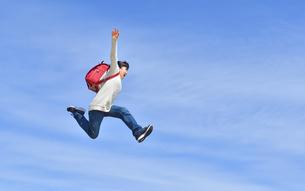 青空でジャンプする小学生の女の子の写真素材 [FYI02915072]
