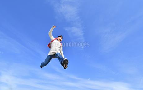 青空でジャンプする小学生の女の子の写真素材 [FYI02915073]