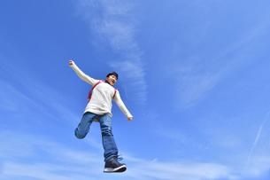 青空でジャンプする小学生の女の子の写真素材 [FYI02915074]