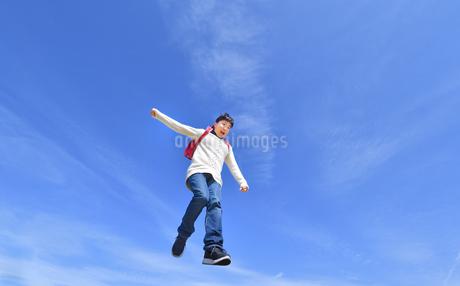 青空でジャンプする小学生の女の子の写真素材 [FYI02915075]