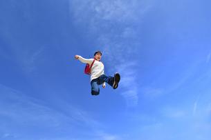 青空でジャンプする小学生の女の子の写真素材 [FYI02915076]