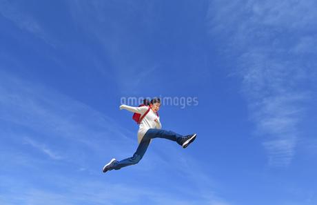 青空でジャンプする小学生の女の子の写真素材 [FYI02915077]