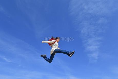 青空でジャンプする小学生の女の子の写真素材 [FYI02915078]