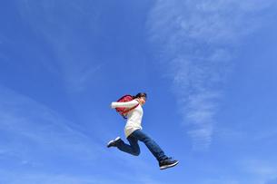 青空でジャンプする小学生の女の子の写真素材 [FYI02915079]