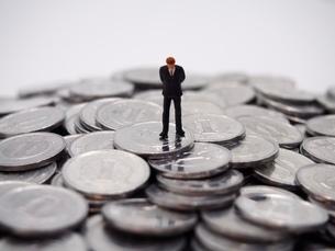 1円玉の山と下を向くビジネスマンの写真素材 [FYI02915148]
