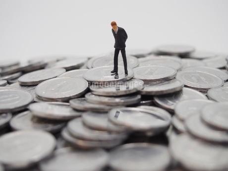 下を向くビジネスマンと1円玉の写真素材 [FYI02915149]