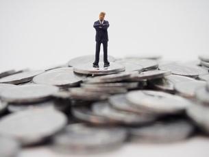 1円玉の山と腕組みをするビジネスマンの写真素材 [FYI02915150]