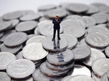 腕組みをするビジネスマンと1円玉の写真素材 [FYI02915151]