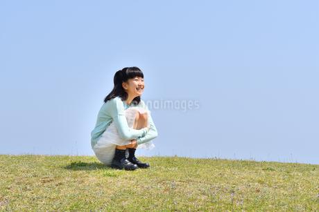 芝生広場に座る女の子(青空)の写真素材 [FYI02915154]
