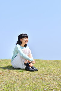 芝生広場に座る女の子(青空)の写真素材 [FYI02915156]