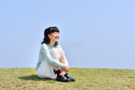 芝生広場に座る女の子(青空)の写真素材 [FYI02915157]