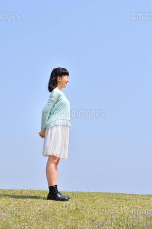 青空で笑う女の子(芝生広場)の写真素材 [FYI02915162]