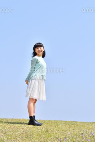 青空で笑う女の子(芝生広場)の写真素材 [FYI02915163]