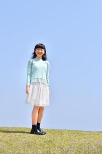 青空で笑う女の子(芝生広場)の写真素材 [FYI02915164]