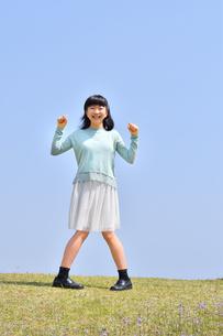 青空で笑う女の子(芝生広場)の写真素材 [FYI02915165]