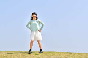 青空で笑う女の子(芝生広場)の写真素材 [FYI02915166]