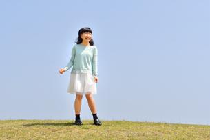 青空で笑う女の子(芝生広場)の写真素材 [FYI02915167]