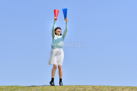 青空で応援する女の子(メガホン、芝生広場)の写真素材 [FYI02917289]