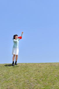 青空で応援する女の子(メガホン、芝生広場)の写真素材 [FYI02917294]