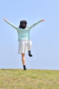 青空で手を広げる女の子(後姿、芝生広場、片足立ち)の写真素材 [FYI02917295]