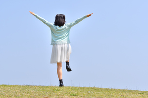 青空で手を広げる女の子(後姿、芝生広場、片足立ち)の写真素材 [FYI02917296]