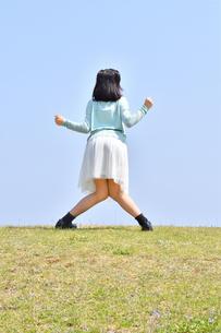 青空でポーズをきめる女の子(後姿、芝生広場)の写真素材 [FYI02917299]