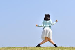 青空でポーズをきめる女の子(後姿、芝生広場)の写真素材 [FYI02917300]