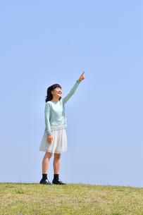 青空で指さす女の子(芝生広場)の写真素材 [FYI02917307]