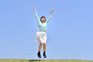 青空でジャンプする女の子(芝生広場)の写真素材 [FYI02917312]