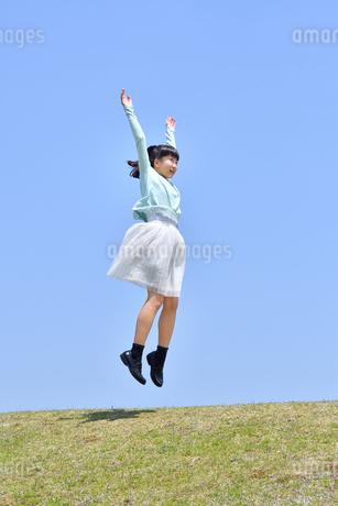 青空でジャンプする女の子(芝生広場)の写真素材 [FYI02917313]
