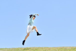 青空でジャンプする女の子(芝生広場)の写真素材 [FYI02917316]