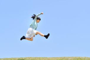 青空でジャンプする女の子(芝生広場)の写真素材 [FYI02917317]