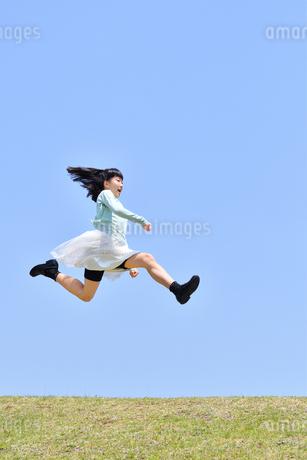青空でジャンプする女の子(芝生広場)の写真素材 [FYI02917318]