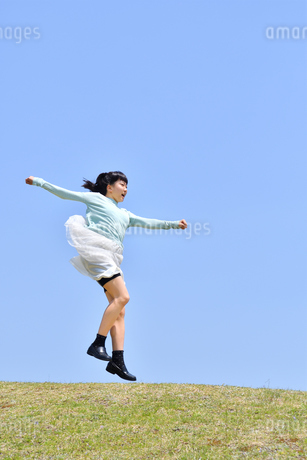 青空でジャンプする女の子(芝生広場)の写真素材 [FYI02917319]
