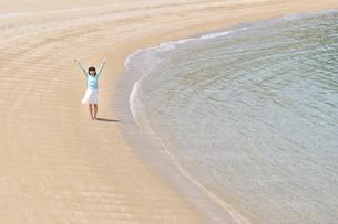 ビーチで手を上げる女の子の写真素材 [FYI02919725]