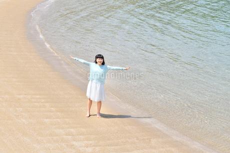 ビーチで手を上げる女の子の写真素材 [FYI02919727]