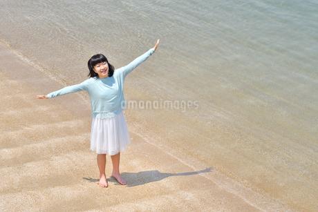 ビーチで手を上げる女の子の写真素材 [FYI02919728]