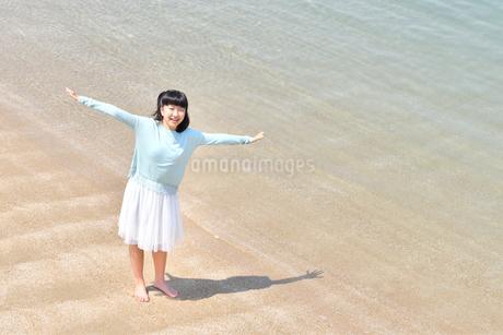 ビーチで手を上げる女の子の写真素材 [FYI02919729]