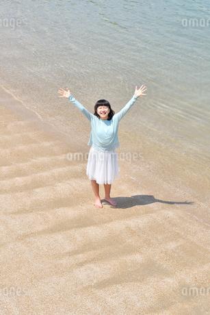 ビーチで手を上げる女の子の写真素材 [FYI02919730]