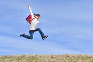 青空でジャンプする小学生の女の子(ランドセル、芝生広場)の写真素材 [FYI02919740]