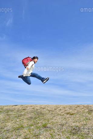 青空でジャンプする小学生の女の子(ランドセル、芝生広場)の写真素材 [FYI02919742]