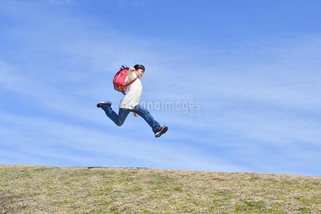 青空でジャンプする小学生の女の子(ランドセル、芝生広場)の写真素材 [FYI02919743]